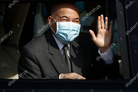 Stock Photo of Cambodia's King Norodom Sihamoni waves from a vehicle to his government civil servants after he lit the victory fire during the country's 67th Independence Day celebration, in Phnom Penh, Cambodia