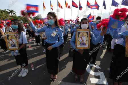 Cambodian students, holding the portrait of King Norodom Sihamoni, participate in the country's 67th Independence Day celebration, in Phnom Penh, Cambodia