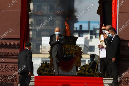 Cambodia's King Norodom Sihamoni, center, greets to his government civil servants after he light the victory fire during the country's 67th Independence Day celebration, in Phnom Penh, Cambodia