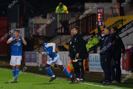 Harrison Burrows of Peterborough United (16) enters the game as Peterborough United Manager Darren Ferguson looks on