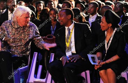 British entrepreneur Richard Branson, left, speaks to South African billionaire Patrice Motsepe, centre, and his wife Precious Makgosi Moloi, right, before the funeral service for former South African President Nelson Mandela in Qunu, South Africa. South African businessman Patrice Motsepe entered the race to be president of the African soccer confederation on