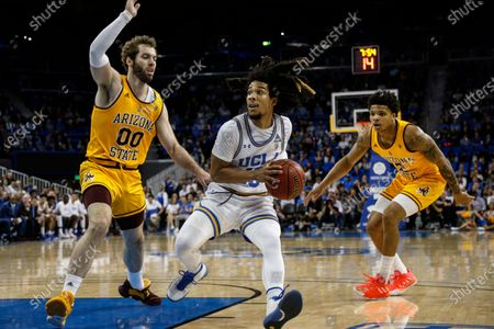Stock Picture of Guard Tyger Campbell (10) drives between Arizona State forward Mickey Mitchell (00) and guard Rob Edwards (2) during an NCAA college basketball game, in Los Angeles. Campbell was the only player to start all 31 games during the 2019-20 season, averaging 8.3 points and five assists, most among the Pac-12's returners