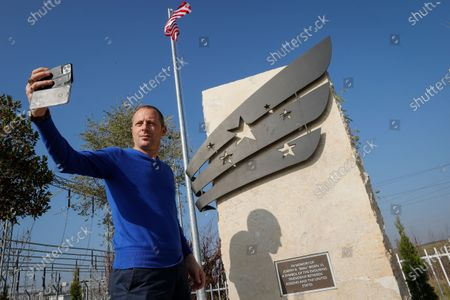 Stock Photo of A Kosovo Albanian man takes a selfie in front of the memorial in honor of elected US President Joe Biden late son, Joseph R. 'Beau' Biden, III, near the US military Camp Bondsteel, in the village of Sojevo, Kosovo, 09 November 2020.