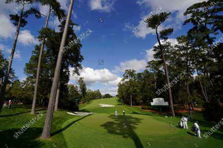 With no spectators in attendance, Fred Couples putts on the 10th green during a practice round for the Masters golf tournament, in Augusta, Ga