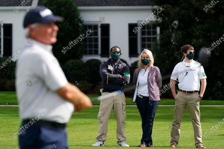 Medical workers watch as Fred Couples tees off on the 10th hole watch during a practice round for the Masters golf tournament, in Augusta, Ga