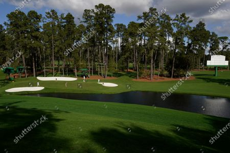 With no spectators on the course, the group of Tommy Fleetwood, of England, Justin Rose, of England, and Collin Morikawa play the 16th hole during a practice round for the Masters golf tournament, in Augusta, Ga
