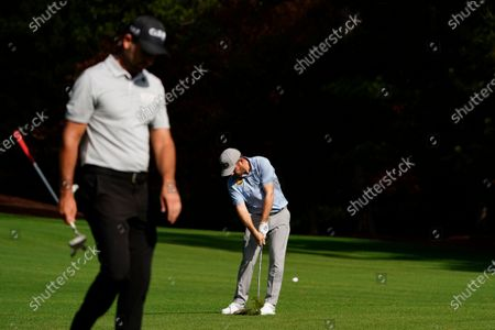 Charl Schwartzel, of South Africa, left, walks past as Louis Oosthuizen, of South Africa, hits on the second fairway during a practice round for the Masters golf tournament, in Augusta, Ga
