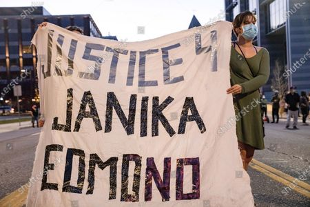 """Demonstrators hold a sheet with the words """"Justice 4 Janika Edmond"""". Janika Edmond was a woman from Adrian, Michigan who committed suicide within the Women's Huron Valley Correctional Facility in Ypsilanti, Michigan. Edmond had made it known to the guards she posed a threat to herself, but the guards did not stop her from committing suicide., Demonstrators turned out in Ann Arbor for the """"Say Her Name: Aura Rosser"""" rally, candlelight vigil and march. The event began at the Ann Arbor City Hall building and looped through the streets of Ann Arbor until demonstrators ended up back at the Ann Arbor City Hall building. This event was in response to the police shooting of Aura Rosser, a black woman who struggled with mental illness. This event takes place almost exactly six years from the day Rosser died."""