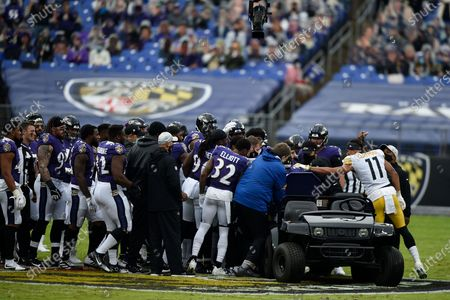 Stock Image of Pittsburgh Steelers wide receiver Chase Claypool (11) approaches a cart as Baltimore Ravens players surround offensive tackle Ronnie Stanley after he suffered an injury during the first half of an NFL football game, in Baltimore