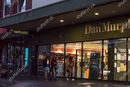 Stock Picture of A group of young adults walk by open Dan Murphy liquor store on Chapel street, one of the most iconic streets of Melbourne.