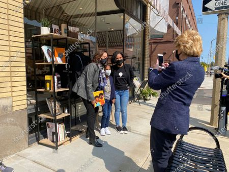 """Michigan Sen. Debbie Stabenow, right, takes a picture of Vice President-elect Kamala Harris posing for a photo on with Egypt Otis and her nine-year-old daughter Eva Allen in front of their downtown Flint, Mich., bookstore, the Comma Bookstore & Social Hub. For countless women and girls, Harris' achievement of reaching the second highest office in the country represents hope, validation and the shattering of a proverbial glass ceiling that has kept mostly white men perched at the top tiers of American government. """"My daughter is going to be a part of history because she had the opportunity to have a conversation with our first Black woman vice president,"""" said Otis. """"It just shows you how important representation is"""