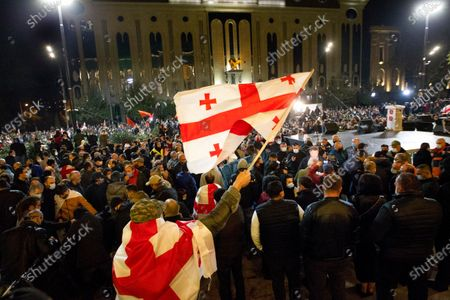 Demonstrators wave Georgian national flags during a rally of supporters of the ex-President Mikhail Saakashvili's United National Movement, protesting the election results in Tbilisi, Georgia, . Some thousands of opposition supporters rallied Monday in ex-Soviet Georgia to demand a snap vote after the opposition accused the ruling party of rigging tightly contested parliamentary elections