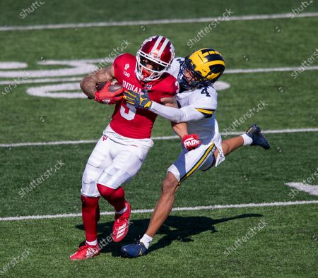 Stock Photo of Indiana wide receiver Ty Fryfogle (3) is wrapped up by Michigan defensive back Vincent Gray (4) during the second half of an NCAA college football game, in Bloomington, Ind. Indiana won 38-21