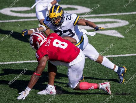 Michigan linebacker Michael Barrett (23) closes in on Indiana running back Stevie Scott III (8) as he runs the ball up field during the second half of an NCAA college football game, in Bloomington, Ind. Indiana won 38-21