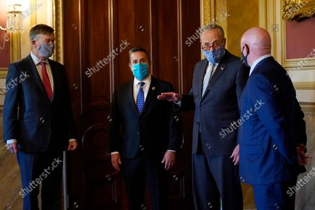 Senate Minority Leader Sen. Chuck Schumer of N.Y., second from right, talks with the newly elected senators, from left, Sen.-elect John Hickenlooper, D-Colo., Sen.-elect Ben Ray Lujan, D-N.M., and Sen.-elect Mark Kelly, D-Ariz., before a meeting on Capitol Hill in Washington