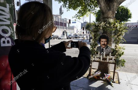 """Stock Picture of Louise Spear of Los Angeles takes a picture of a shrine set up for the late """"Jeopardy"""" quiz show host Alex Trebek near his star on the Hollywood Walk of Fame, in Los Angeles. Trebek died Sunday of pancreatic cancer at age 80"""
