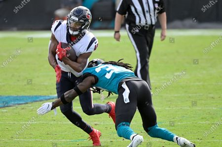 Houston Texans wide receiver Randall Cobb (18) is tackled by Jacksonville Jaguars cornerback Tre Herndon after catching a pass during the first half of an NFL football game, in Jacksonville, Fla