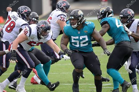 Jacksonville Jaguars defensive tackle DaVon Hamilton (52) pursues a play in front of Houston Texans center Nick Martin (66) during the second half of an NFL football game, in Jacksonville, Fla