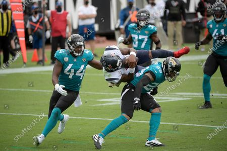 Houston Texans quarterback Deshaun Watson, center, is upended by Jacksonville Jaguars safety Josh Jones (29) and linebacker Myles Jack (44) after diving for the end zone during the first half of an NFL football game, in Jacksonville, Fla