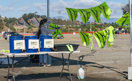 Personal protective equipment (PPE) hangs to dry after being decontaminated, as drivers with an appointment wait in line to get a free of charge COVID-19 virus self-test at Dodger Stadium, with the capacity to test 6,000 Angelenos a day in Los Angeles on . Testing company Curative and Sean Penn's non-profit Community Organized Relief Effort: CORE Response are stepping up to meet increased demand providing free COVID-19 testing throughout California, in partnership with local governments and community-based organizations