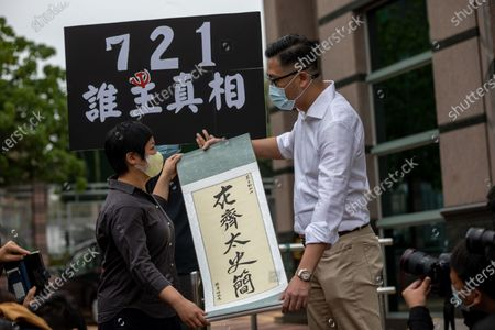Radio Television Hong Kong reporter Bao Choy Yuk-ling (L) receives a calligraphy from Democratic Party lawmaker Lam Cheuk-ting, (R) outside the Fanling Magistrates' Courts in Hong Kong, China, 10 November 2020. Choy has been charged with making false statements under the Road Traffic Ordinance when she was tracing those behind the vicious mob attack in Yuen Long on July 21 last year. Choy was released on bail.