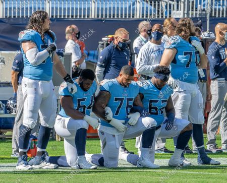 Tennessee Titans offensive tackle Dennis Kelly (71), and offensive tackle Ty Sambrailo (70) show support of offensive guard Nate Davis (64), offensive guard Rodger Saffold III (76), and center Aaron Brewer (62) as they take a knee during the National Anthem of an NFL football game against the Chicago Bears, in Nashville, Tenn