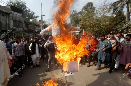 Pakistani railway workers burn an effigy of French President Emmanuel Macron during a protest against Macron and republishing in France of caricatures of the Prophet Muhammad they deem blasphemous, in Lahore, Pakistan