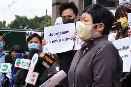 """A supporter holds a placard reading """"Journalist is not a crime"""" while Bao Choy-yuk Ling, a freelance journalist speaks to the media at the Fanling Magistrates' Court for a hearing. Bao Choy-yuk Ling, a freelance journalist who worked with Hong Kong's public broadcaster RTHK (Radio Television Hong Kong) on investigations into the July 21 Yuen Long mob attack, arrives wearing a facemask at Fanling Magistrates' Court for a hearing. Choy was arrested for making a false statement related to her investigation into suspected persons involved in the Yuen Long mob attack for a RTHK TV documentary."""