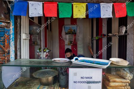 Man wearing a mask to protect himself from the coronavirus works at a stall displaying a photo of Tibetan spiritual leader the Dalai Lama in Dharmsala, India