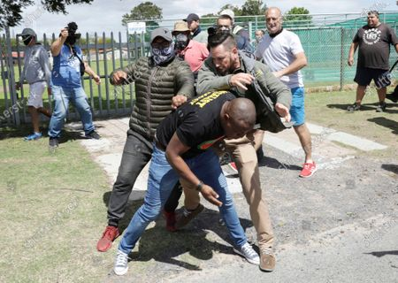 Stock Photo of Member of the leftist opposition party Economic Freedom Fighters, front, is attacked while protesting outside the Brackenfell High School, near Cape Town, South Africa, . South African president Cyril Ramaphosa has called for restraint following clashes at an anti-racism protest outside a school in Cape Town. Members of the leftist opposition party Economic Freedom Fighters protested in front of the Brackenfell High School over allegations that a graduation event was attended only by white pupils