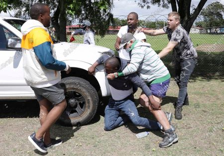 Stock Image of Members of the leftist opposition party Economic Freedom Fighters are attacked while protesting outside the Brackenfell High School, near Cape Town, South Africa, . South African president Cyril Ramaphosa has called for restraint following clashes at an anti-racism protest outside a school in Cape Town. Members of the leftist opposition party Economic Freedom Fighters protested in front of the Brackenfell High School over allegations that a graduation event was attended only by white pupils