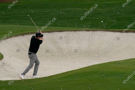 Justin Rose, of England, hits out of a bunker on the fourth hole during a practice round for the Masters golf tournament, in Augusta, Ga