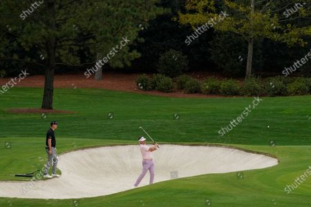 Justin Rose, of England, watches as Ian Poulter, of England, hits out of a bunker on the fourth hole during a practice round for the Masters golf tournament, in Augusta, Ga