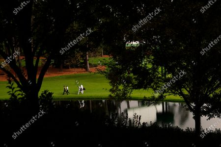 Jimmy Walker and C.T. Pan, of Taipei, walk to the 16th green with their caddies during a practice round for the Masters golf tournament, in Augusta, Ga