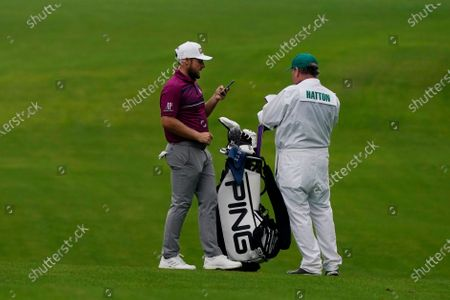Tyrrell Hatton, of England, speaks to his caddie on the seventh fairway during a practice round for the Masters golf tournament, in Augusta, Ga