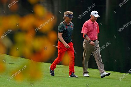 Bernhard Langer, left, of Germany, walks with Sandy Lyle, of Scotland on the 15th hole during a practice round for the Masters golf tournament, in Augusta, Ga