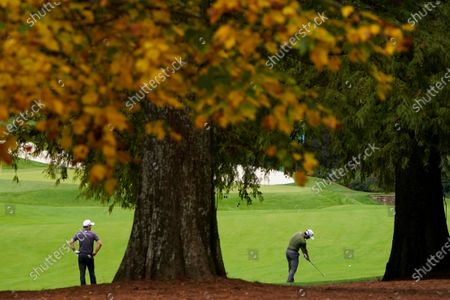 Nick Taylor, of Canada, watches as Tyrrell Hatton, of England, hits on the 13th fairway during a practice round for the Masters golf tournament, in Augusta, Ga