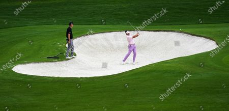Justin Rose of England (L) watches as Ian Poulter of England hits out of a bunker on the fourth hole during the second practice round of the 2020 Masters Tournament at the Augusta National Golf Club in Augusta, Georgia, USA, 10 November 2020. After being delayed seven months by the coronavirus pandemic, the 2020 Masters Tournament is being held without patrons 12 November through 15 November.