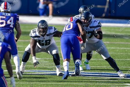 Seattle Seahawks guard Damien Lewis (68) and center/guard Ethan Pocic (77) block against Buffalo Bills defensive lineman Quinton Jefferson (90) during the first half of an NFL football game, in Orchard Park, N.Y