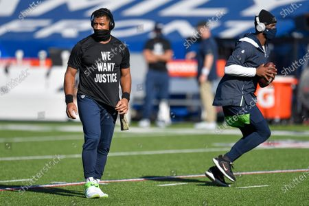 Seattle Seahawks quarterbacks Russell Wilson, left, and Geno Smith warm up before an NFL football game, in Orchard Park, N.Y