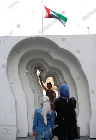 A woman takes a photo of an artwork of 'Sheikh Mohammed's three-finger salute' during the Dubai Design Week at the Dubai Design District (d3) in the Gulf emirate of Dubai, United Arab Emirates, 10 November 2020. The three-finger hand gesture was coined as a logo for the UAE by Dubai's ruler Sheikh Mohammed bin Rashid Al Maktoum in February 2013, and means Win, Victory, and Love. The Dubai Design District (d3) returned to host events after the lifting of the COVID-19 coronavirus lockdown, such as Dubai Design Week, which runs until 14 November 2020.