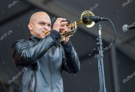 Irvin Mayfield performs at the New Orleans Jazz and Heritage Festival in New Orleans. Mayfield and his musical partner, pianist Ronald Markham, each pleaded guilty, to a conspiracy to commit fraud charge. The federal charge stemmed from the time the two spent as board members of the charitable New Orleans Public Library Foundation. Prosecutors alleged that they steered more than $1.3 million raised for public libraries to themselves by funneling it through the New Orleans Jazz Orchestra, which Mayfield founded