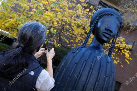 University of Pennsylvania employee takes a picture of a newly installed sculpture by artist Simone Leigh on the University campus in Philadelphia, . Leigh's 16-foot-tall bronze bust of a Black woman has been installed at the entrance to the heart of the University of Pennsylvania's campus