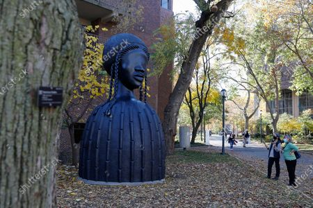People look at a newly installed sculpture by artist Simone Leigh on the University campus in Philadelphia, . Leigh's 16-foot-tall bronze bust of a Black woman has been installed at the entrance to the heart of the University of Pennsylvania's campus