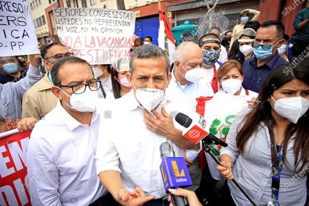 Former Peruvian President Ollanta Humala (C) speaks to the press as demonstrators protest in Lima, Peru, 10 November 2020. Hundreds of protesters gathered in downtown Lima and marched towards Congress in protest against the imminent swearing-in of its incumbent, Manuel Merino, as new President of Peru, following the removal of Martín Vizcarra. The banner reads 'right of insurgency'.