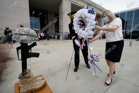 Adjutant General Janson D. Boyles, left, and Gold Star mother Pam Presley Tolbert, carry a memorial wreath to the Fallen Soldier Battle Cross, at a Veterans Day Celebration honoring Mississippians who serve and have served in the United States Armed Forces, at the Two Mississippi Museums in Jackson, Miss. Tolbert's son, Marine Corps Cpl. Michael Brandon Presley was killed in 2005 while serving in Iraq