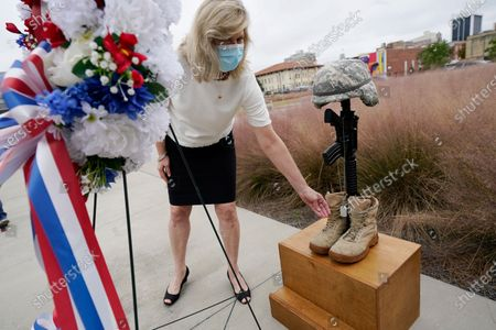 Stock Image of Gold Star mother Pam Presley Tolbert inspects the dog tags attached to the Fallen Soldier Battle Cross, at a Veterans Day Celebration honoring Mississippians who serve and have served in the United States Armed Forces, at the Two Mississippi Museums in Jackson, Miss. Tolbert's son, Marine Corps Cpl. Michael Brandon Presley was killed in 2005 while serving in Iraq