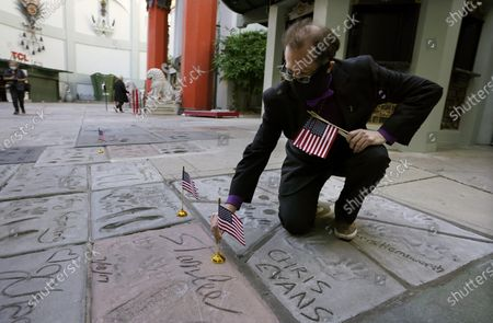 Levi Tinker, theatre operations manager for the TCL Chinese Theatre, lays an American flag down on the hand and footprints of the late comic book legend Stan Lee, in Los Angeles. Flags were placed on the hand and footprints of Hollywood stars who served in their country's military