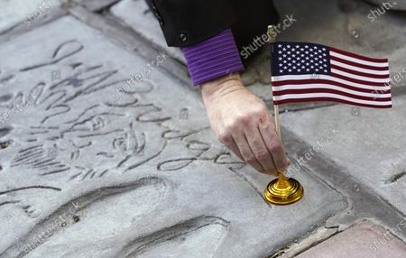 Levi Tinker, theatre operations manager for the TCL Chinese Theatre, lays an American flag down on the hand and footprints of actor Jeff Bridges, in Los Angeles. Flags were placed on the hand and footprints of Hollywood stars who served in their country's military
