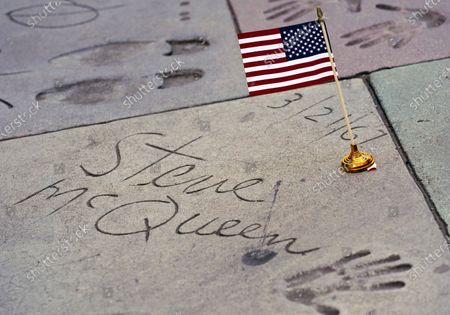 An American flag is placed on the hand and footprints of the late actor Steve McQueen, at the TCL Chinese Theatre forecourt in Los Angeles. Flags were laid down on the hand and footprints of Hollywood stars who served in their country's military